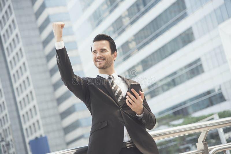 Biznesmen używa telefon komórkowego i uśmiechniętego szczęśliwego z podnieceniem obraz stock