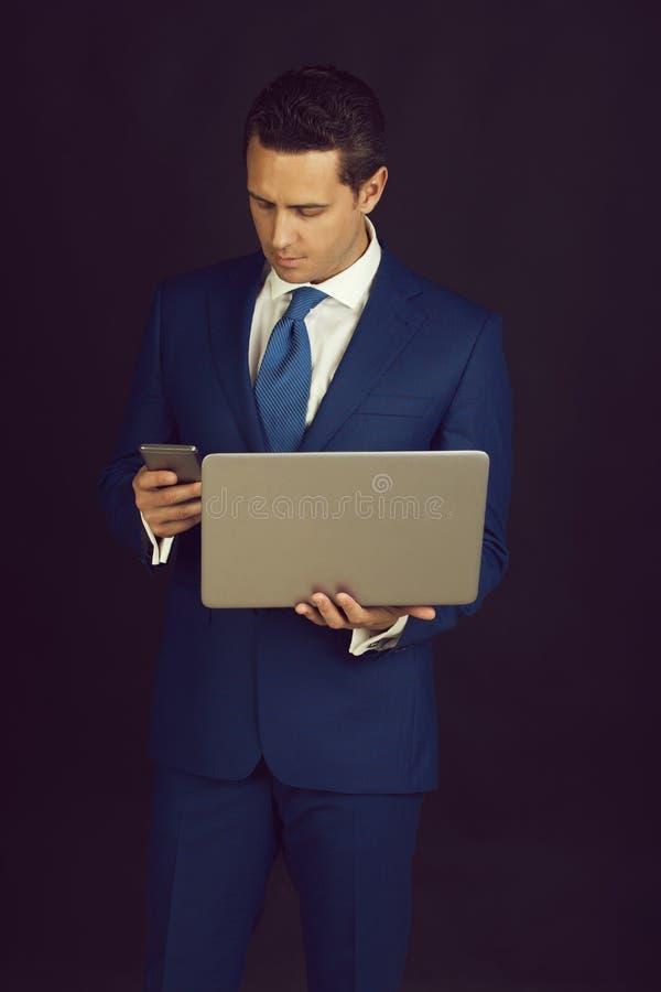 Biznesmen używa telefon komórkowego podczas gdy pracujący na laptopie obrazy royalty free