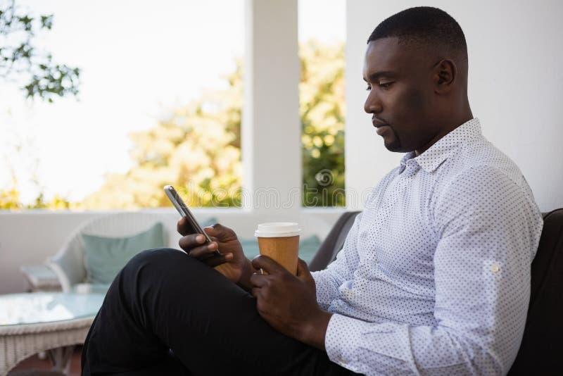 Biznesmen używa telefon komórkowego w kawiarni podczas gdy pijący kawę zdjęcia stock