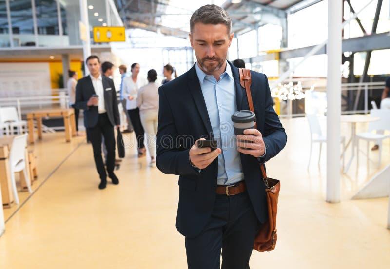 Biznesmen używa telefon komórkowego w korytarzu podczas gdy chodzący zdjęcie royalty free
