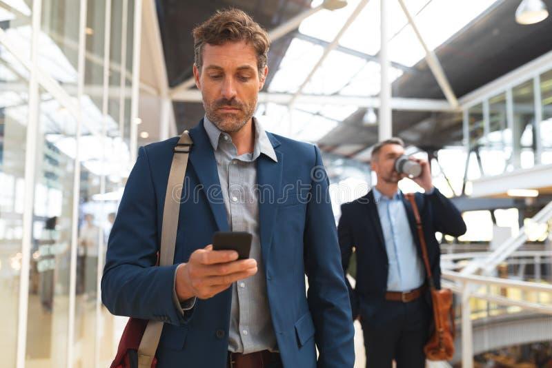 Biznesmen używa telefon komórkowego w korytarzu podczas gdy chodzący fotografia royalty free