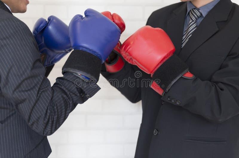 Biznesmen uderza pięścią eac w kostiumu z czerwonymi i błękitnymi bokserskimi rękawiczkami obrazy stock
