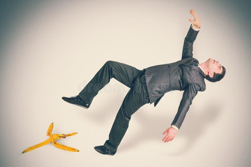 Biznesmen wśliznie i spada od bananowej łupy zdjęcia stock