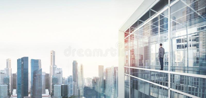Biznesmen wśrodku drapacza chmur, lookng przy miastem obraz royalty free