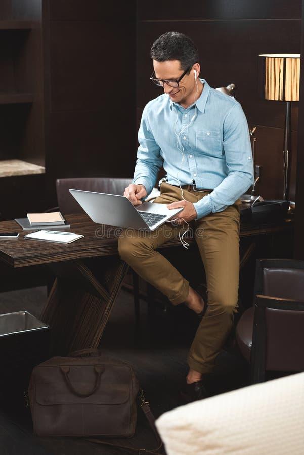 biznesmen w biznesowym przypadkowej odzieży obsiadaniu na biurku i używać zdjęcia stock