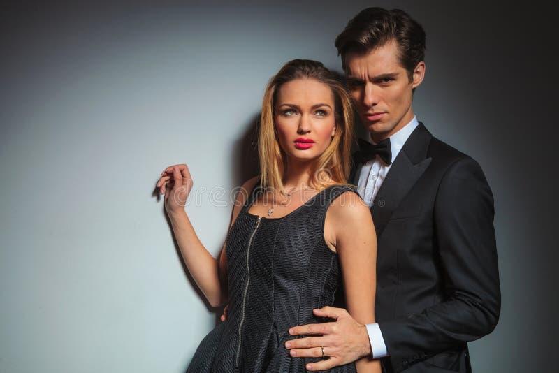Biznesmen w czarnej obejmowanie kobiecie od behind zdjęcia royalty free