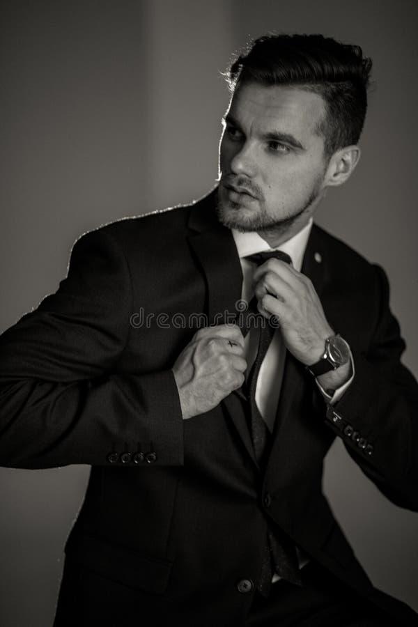 Biznesmen w czarnym kostiumu i białej koszula prostuje h obraz royalty free