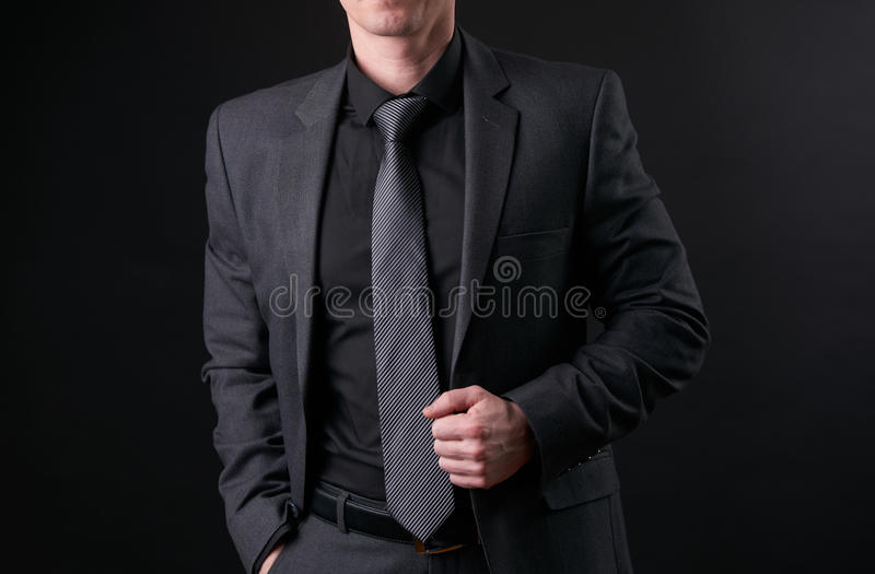 Biznesmen w czarnym, modnym, nowożytnym i eleganckim kostiumu, trzyma rękę w pocke obrazy royalty free