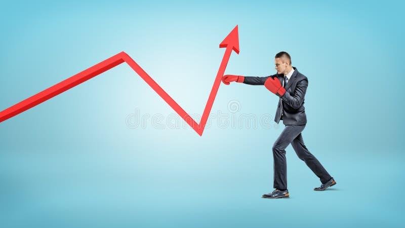Biznesmen w czerwonych bokserskich rękawiczkach uderza pięścią czerwona statystyki arrowed linię robić mu podnosić up fotografia stock