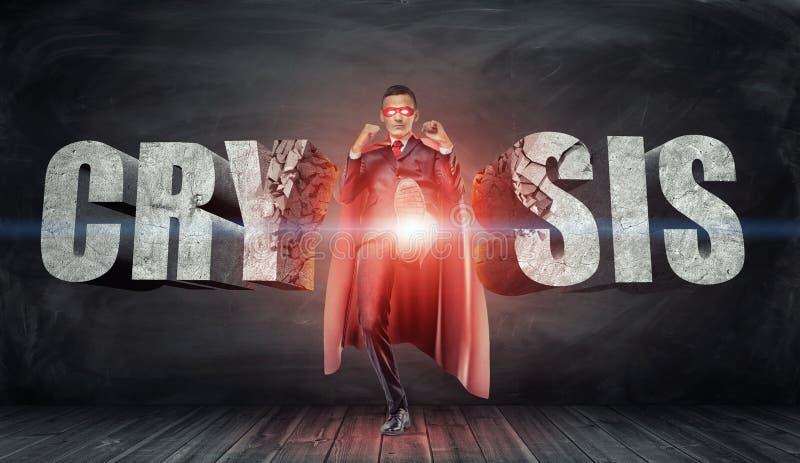 Biznesmen w czerwonym przylądku i maskowym kopanie betonie pisze list czytelniczego ` Crysis ` z jego stopą obraz royalty free