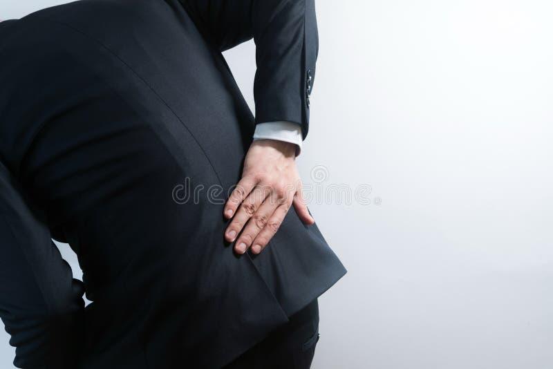 Biznesmen w kostiumu ma backache Zginać w bólu z rękami trzyma niskimi z powrotem zdjęcia royalty free