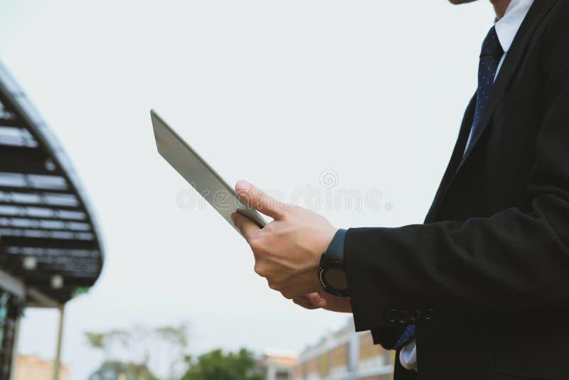 Biznesmen w kostiumu mienia touchpad podczas gdy stojący na zewnątrz buil zdjęcie royalty free