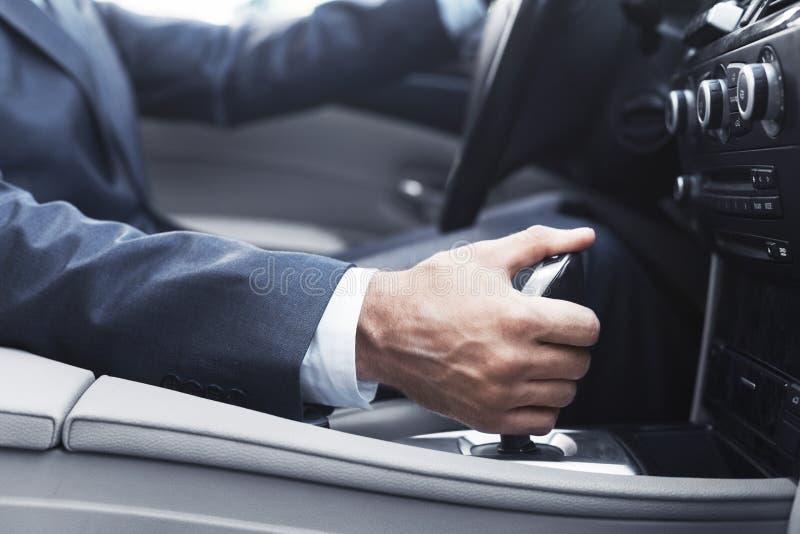 Biznesmen w kostiumu odmieniania przekładni w samochodzie obraz royalty free