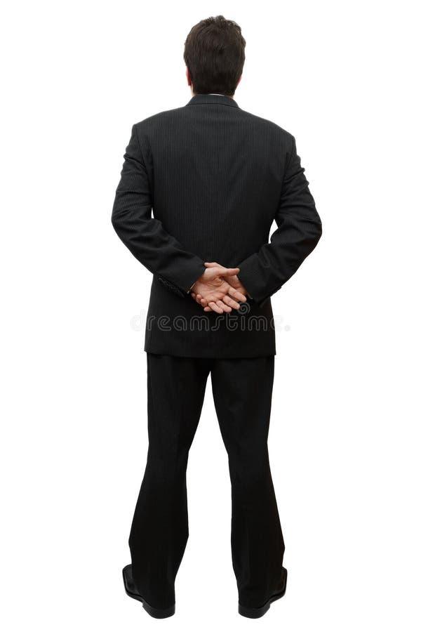 Biznesmen w kostiumu trwanie z powrotem odosobnionym obrazy royalty free