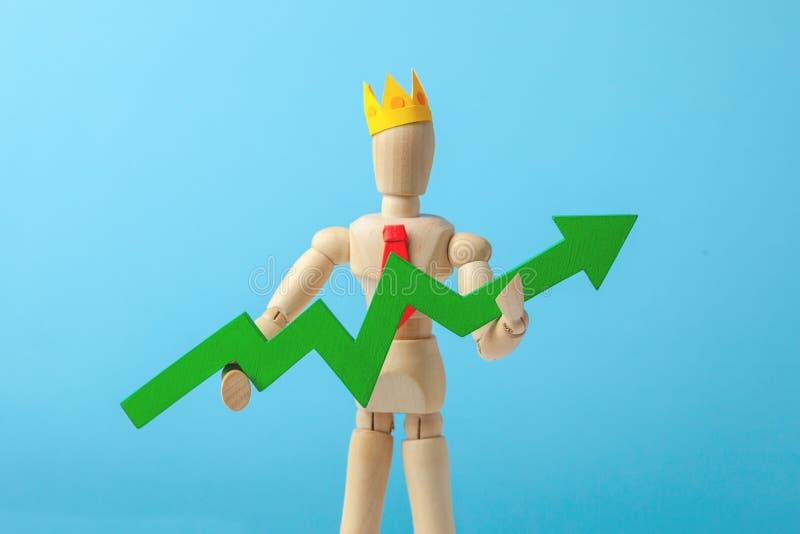 Biznesmen w krawata i korony mieniu zielenieje strzałę na w górę błękitnego tła Dobry kierownik robi przyrosta inwestycja lub inw obrazy stock