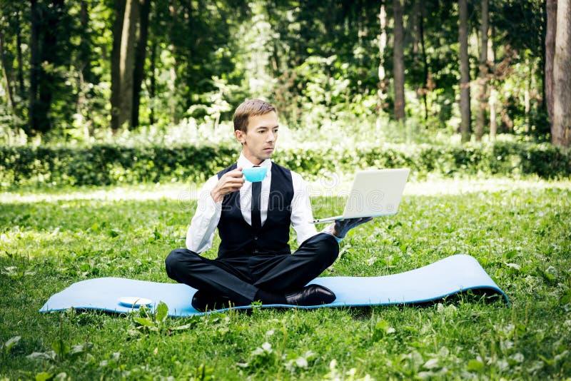 Biznesmen w parku w pozycji lotus nie może się rozluźnić, w jednej ręce trzyma laptopa w drugiej kubek zdjęcie royalty free