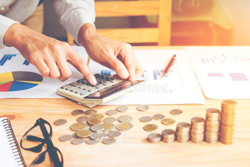 Biznesmen w popielatym koszulowym ręki mieniu, obliczeniu z kalkulatorem i Pieniężnych dane, analizuje wewnątrz i liczy na kalkul zdjęcie royalty free
