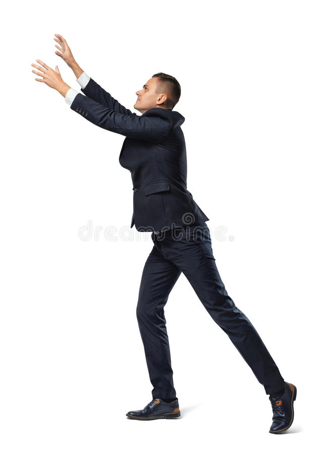 Biznesmen w profilu z jego nogą ustawiającą z powrotem i rękami up w łapanie pozie, odosobnionej na białym tle obrazy royalty free