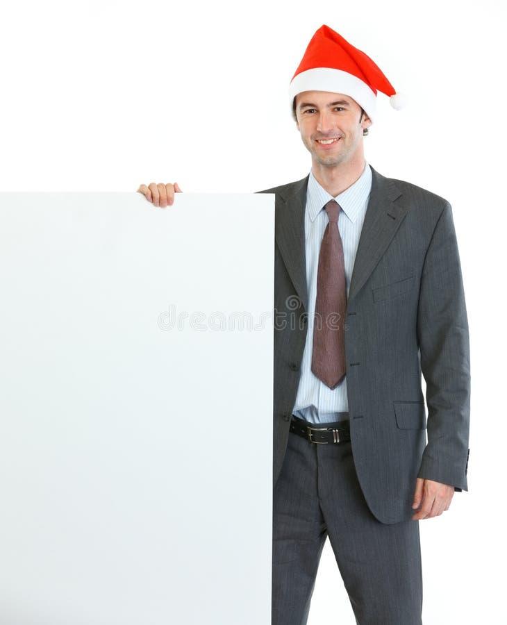 Biznesmen w Santas billboardzie kapeluszowym pokazywać pustym zdjęcie stock