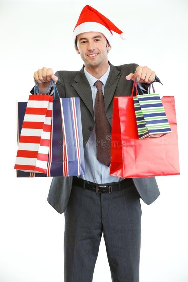 Biznesmen w Santas kapeluszu pokazywać torba na zakupy obrazy royalty free