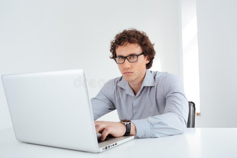 Biznesmen w szkła działaniu na laptopie zdjęcia royalty free
