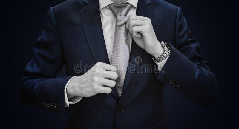 Biznesmen w zmroku - błękitny kostium wiąże popielatego krawat na błękitnym tle obrazy royalty free