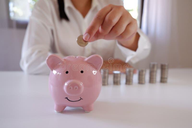 Biznesmen Wkłada monety W prosiątko banku Z stertą monety Nad biurkiem zdjęcie stock
