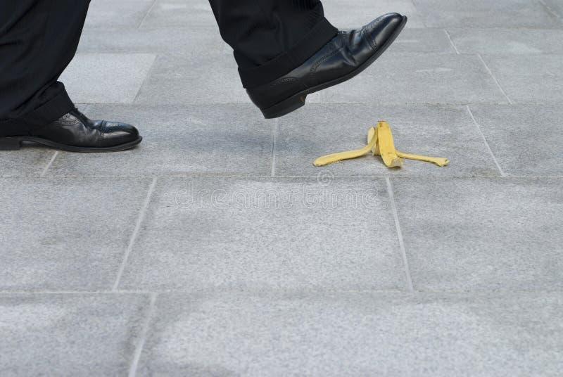 Biznesmen wokoło kroczyć na bananowej skórze zdjęcia stock