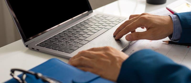 Biznesmen wręcza ruchliwie używa laptop przy biurowym biurkiem obraz royalty free