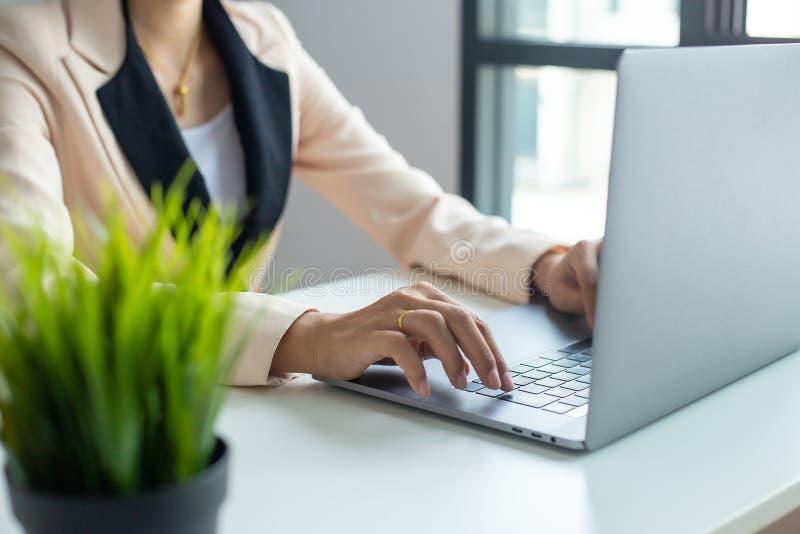 Biznesmen wr?cza ruchliwie u?ywa laptop przy biurowym biurkiem obraz royalty free