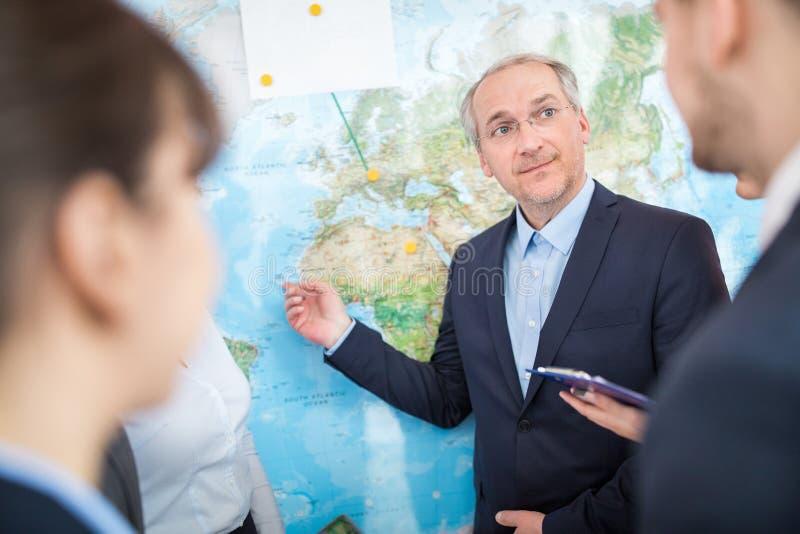 Biznesmen Wskazuje Na mapie Podczas gdy Dyskutujący Z kolegami obrazy stock