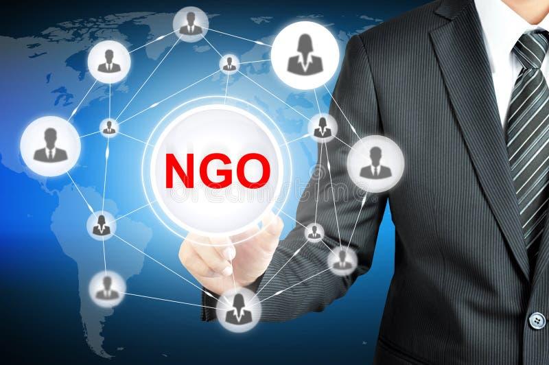 Biznesmen wskazuje na NGO znaku na wirtualnym ekranie (pozarządowa organizacja) ilustracji