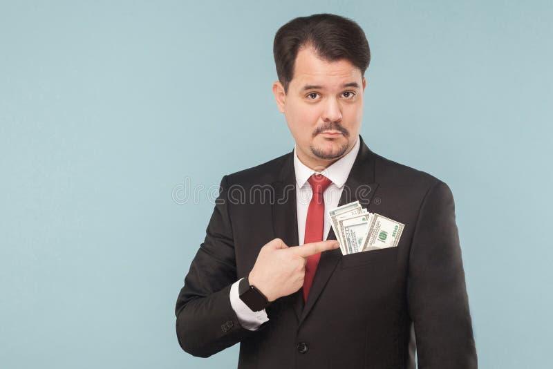 Biznesmen wskazuje palec przy pieniądze w kieszeni łapówka zdjęcia stock