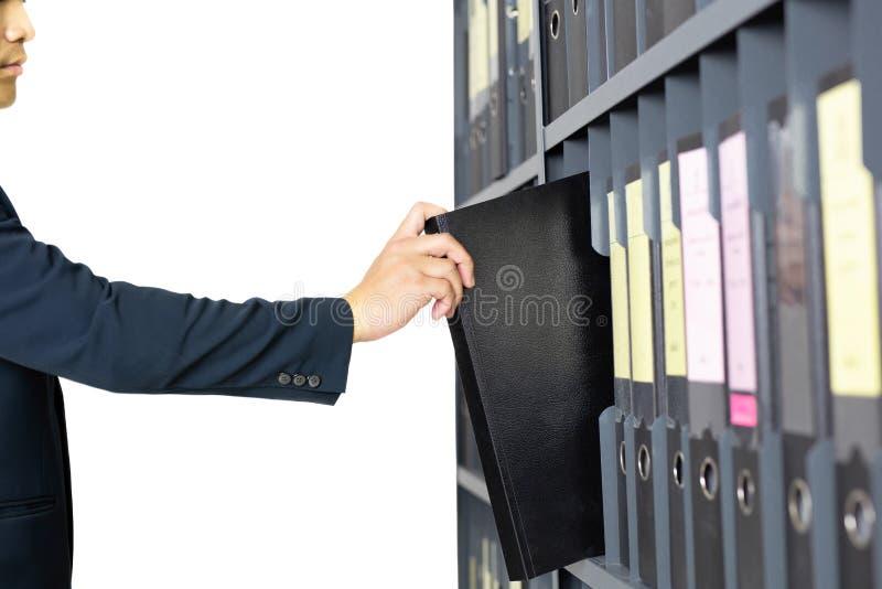 Biznesmen wybiera falcówkę od półek z biuro kartotekami odizolowywać zdjęcia stock