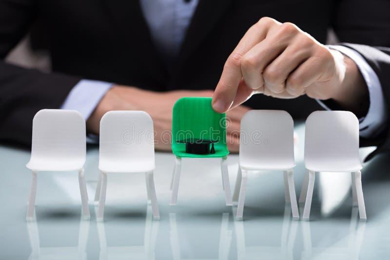 Biznesmen Wybiera Zielonego krzesła Z skalowanie kapeluszem zdjęcia stock