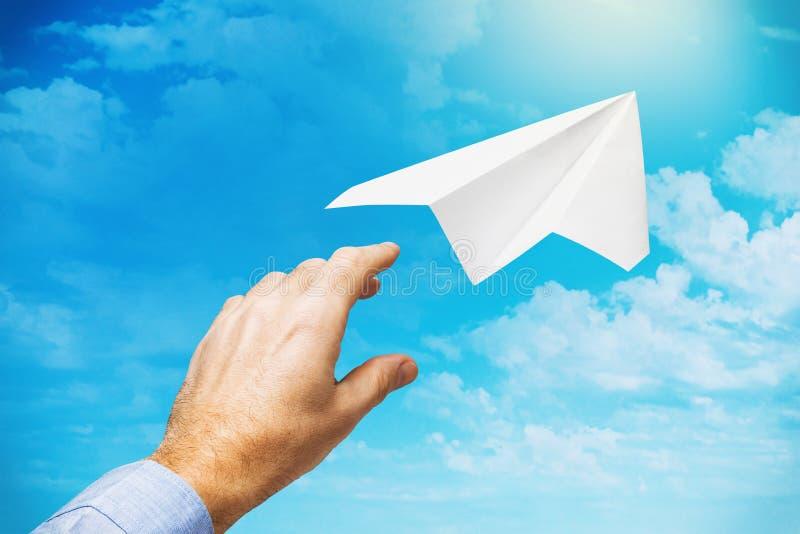 Biznesmen wystrzelił papierową płaszczyznę w niebo jako symbol rozpoczęcia nowej działalności i dążenia do przodu zdjęcie royalty free