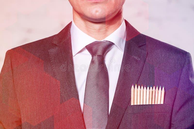 Biznesmen z barwionymi ołówkami w kieszeni przeciw ścianie obraz stock