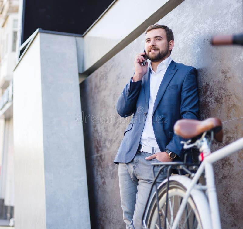 Biznesmen z biznesową rozmową, bicykl blisko obraz royalty free