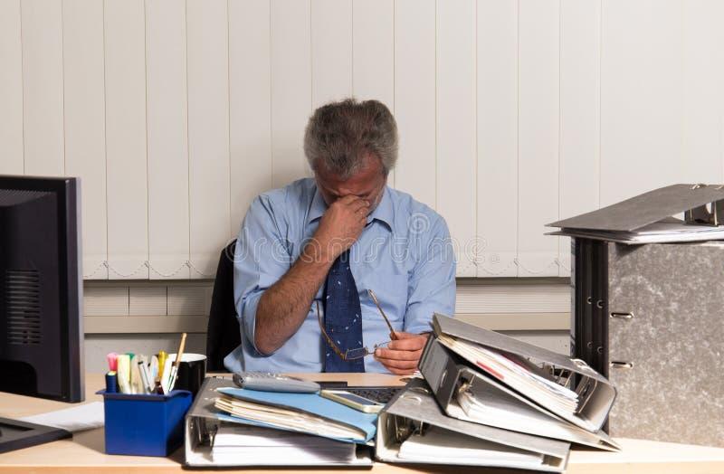 Biznesmen z burnout overstressed przy jego biurowym biurkiem zdjęcia royalty free