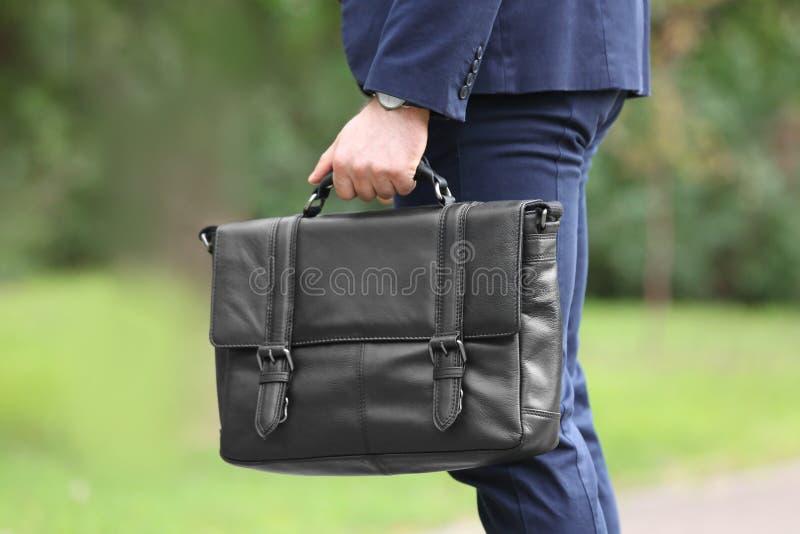 Biznesmen z czarną teczką w ręce outdoors zdjęcia royalty free