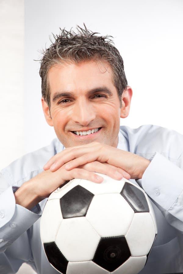 Biznesmen z futbolem przy pracą obrazy stock