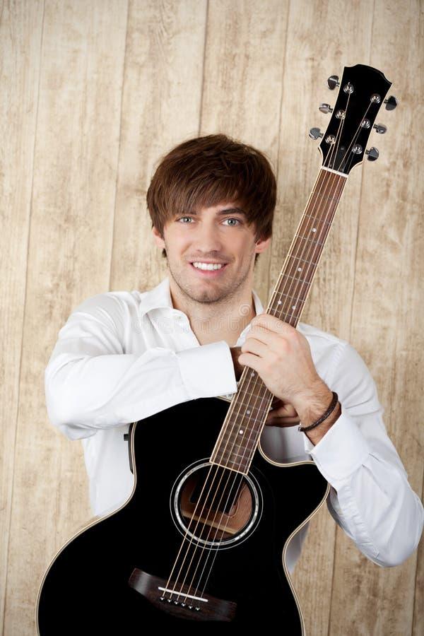 Biznesmen Z gitary pozycją Przeciw Drewnianej ścianie obrazy stock