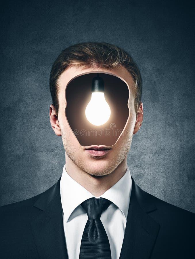 Biznesmen z lampy inside jego głowa na szarość zdjęcia stock
