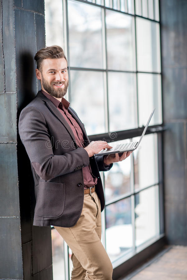 Biznesmen z laptopem Blisko okno obrazy royalty free