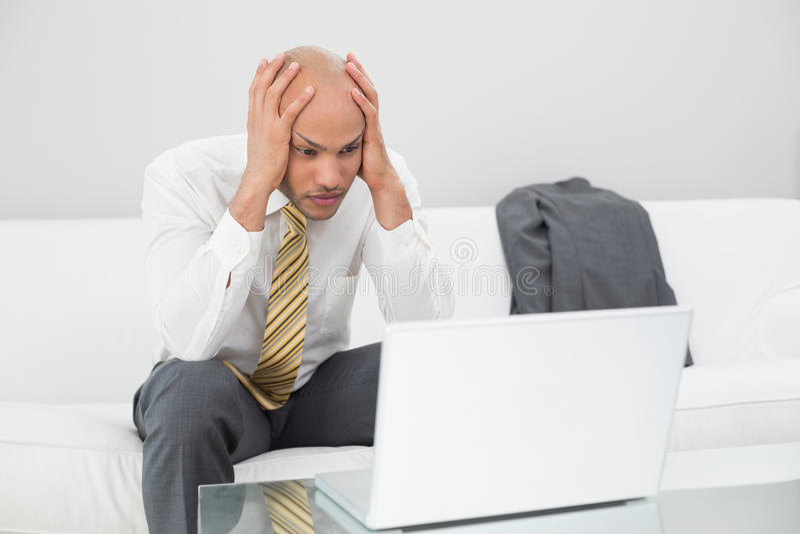 Biznesmen z laptopu mienia głową w rękach w domu zdjęcia stock