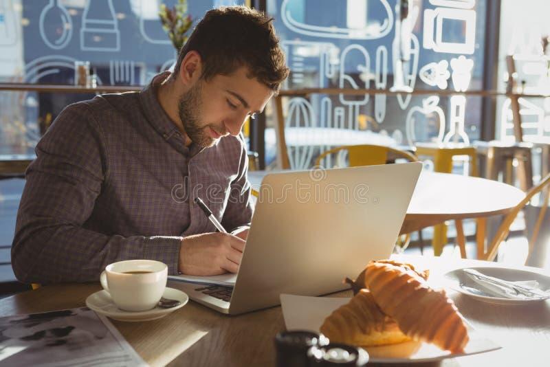 Biznesmen z laptopu writing na papierze w kawiarni zdjęcia stock