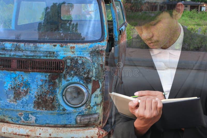 Biznesmen z notepad ręki podpisywania dokumentami w garażu, dwoistego ujawnienia pojęcie zdjęcie stock
