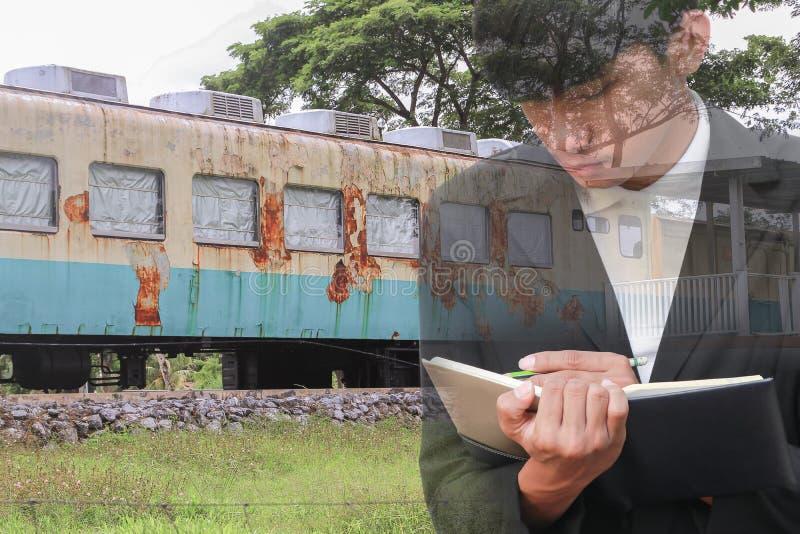 biznesmen z notepad ręki podpisywania dokumentami w pociąg naprawie, dwoistego ujawnienia pojęcie obrazy stock