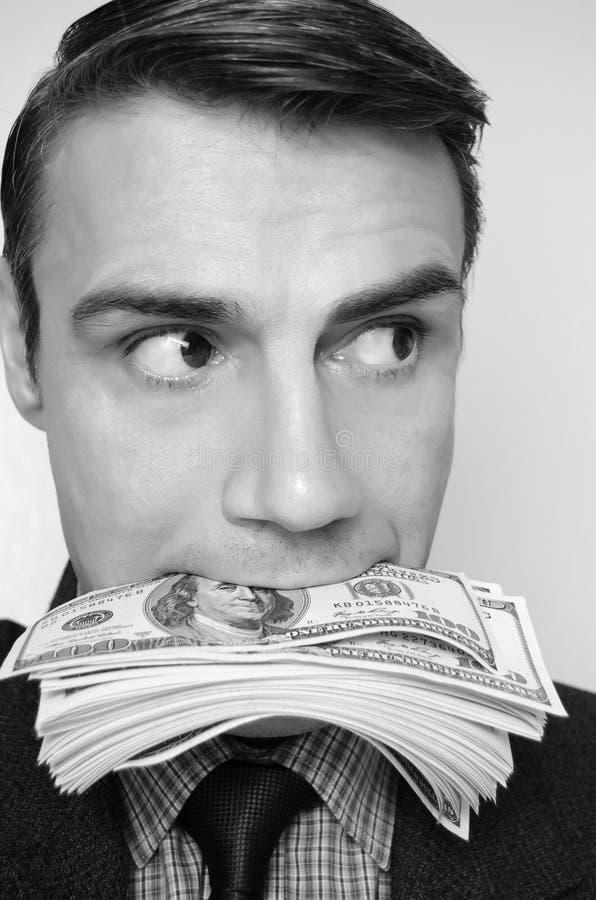 Biznesmen z paczką dolary w usta zdjęcie royalty free