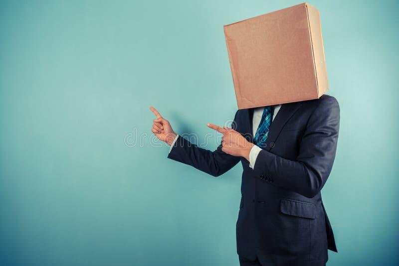 Biznesmen z pudełkiem na głowie wskazuje zdjęcie royalty free